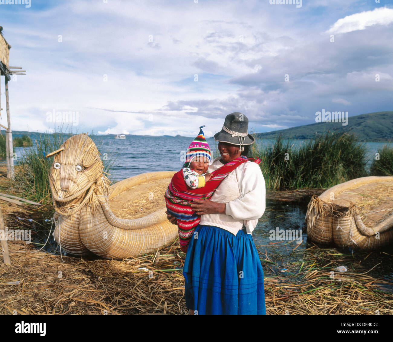 Uru indian mother and child and totora reeds boat. Titicaca Lake. Peru - Stock Image