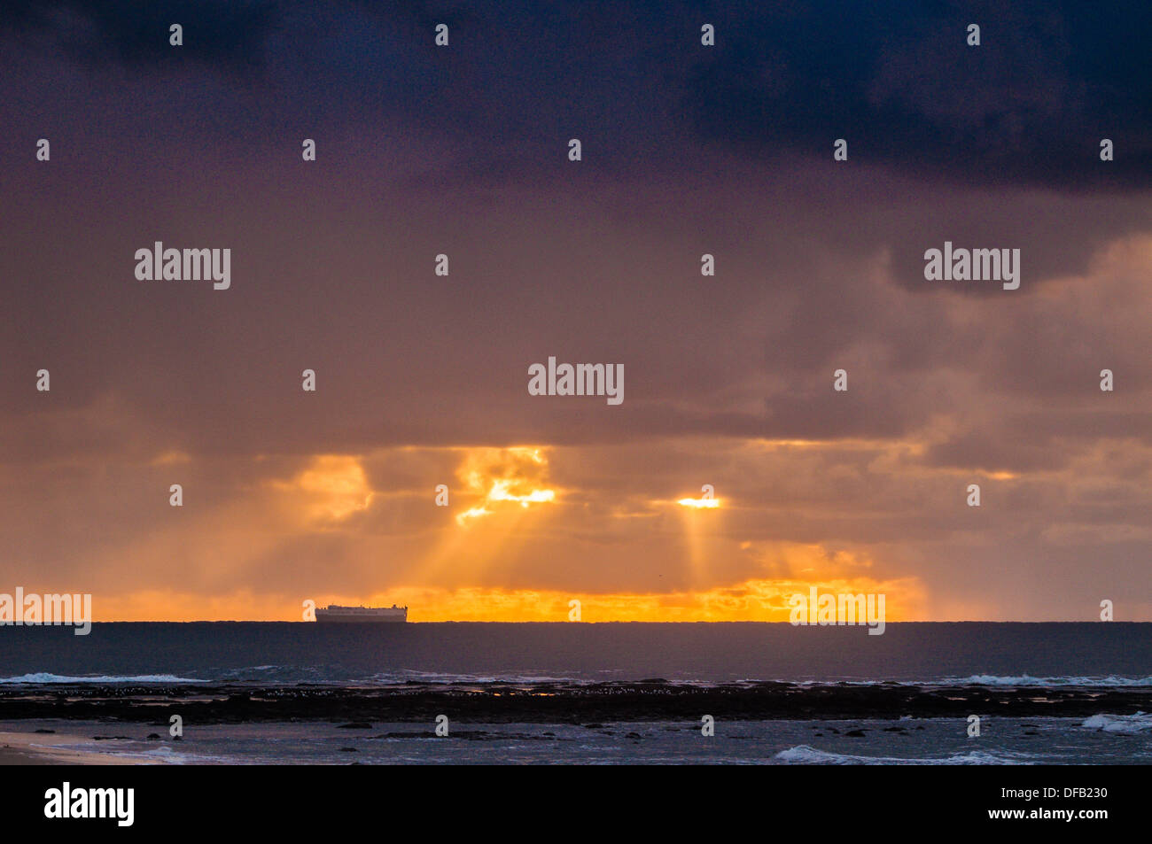 Container ship off the coast as the sunrises, Flat Rock, NSW, Australia - Stock Image