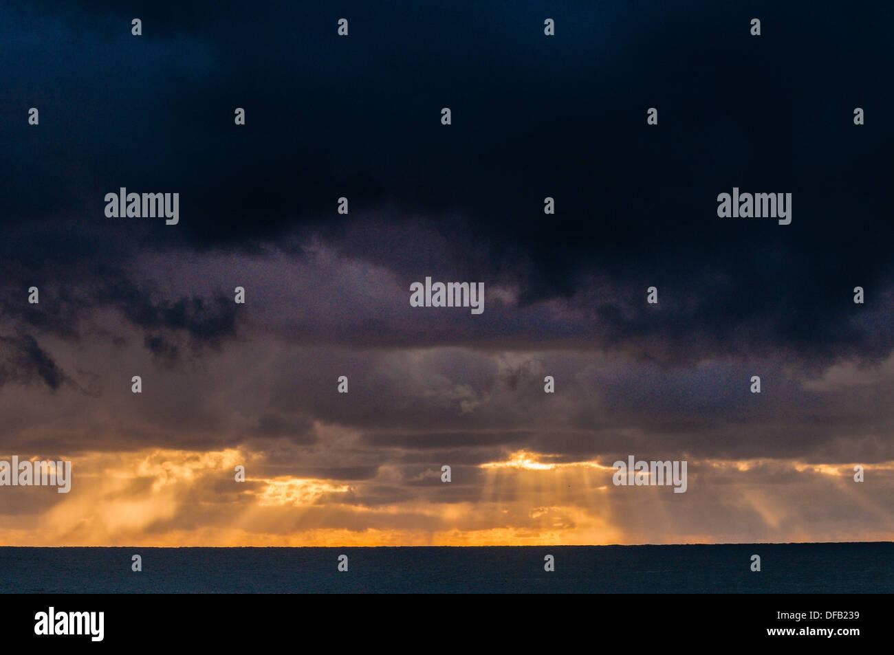 Sunrise & sunbeams off the coast of Flat Rock, NSW, Australia - Stock Image