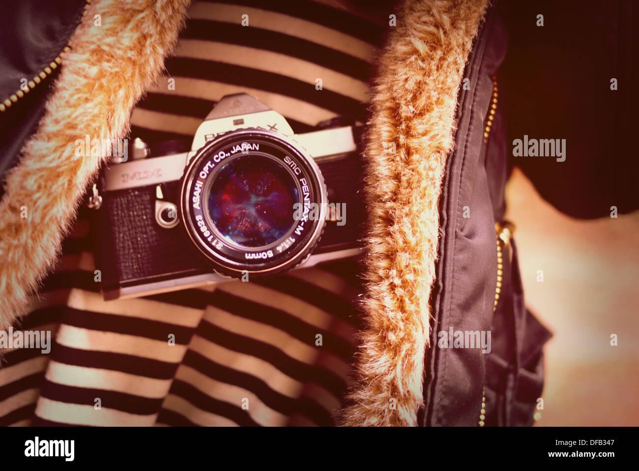 old Pentax MX camera hanging on girl - Stock Image