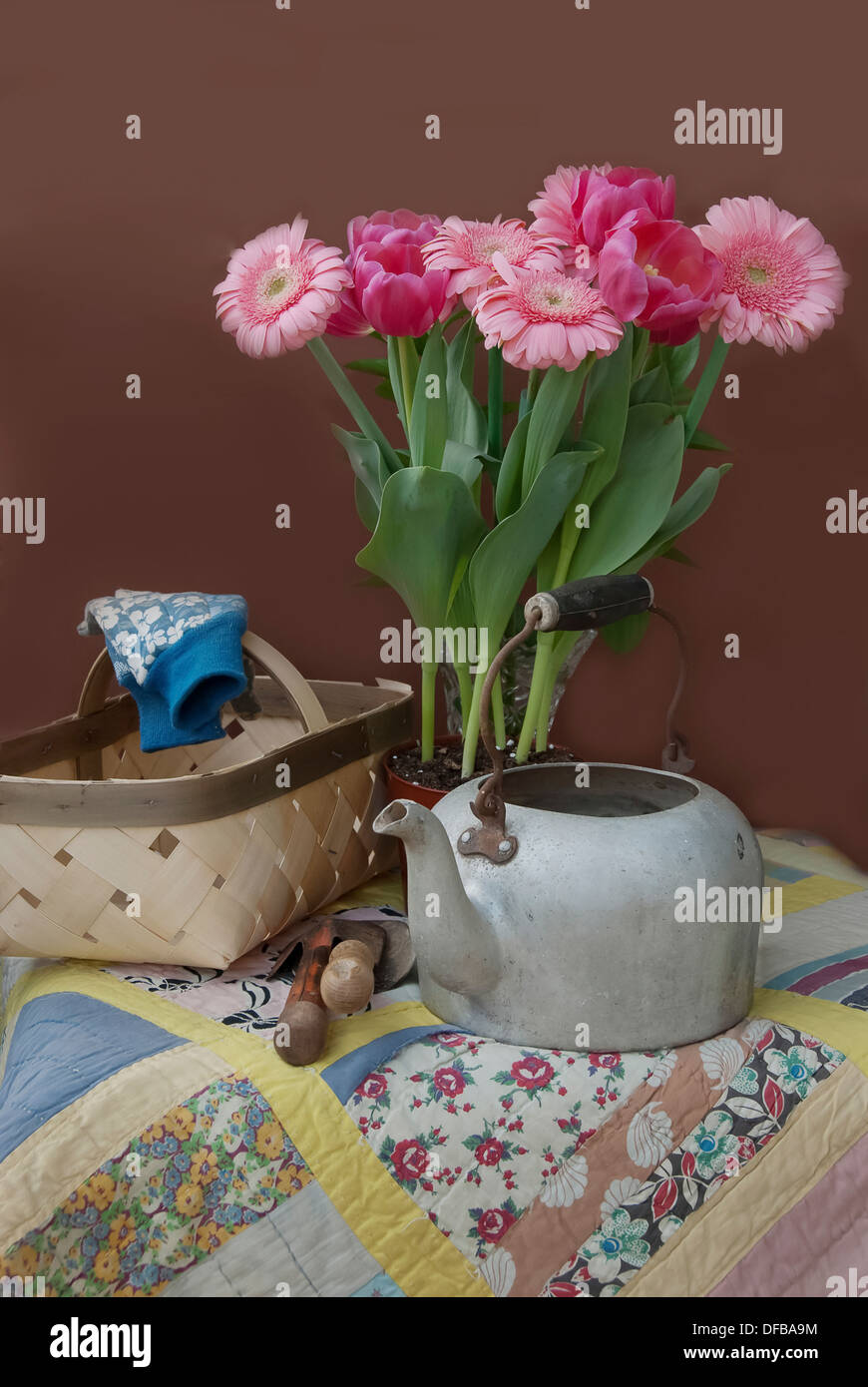 A basket, an old tea pot, gloves, gardening tools, pink tulips, pink gerber daisies on a hand made quilt. - Stock Image
