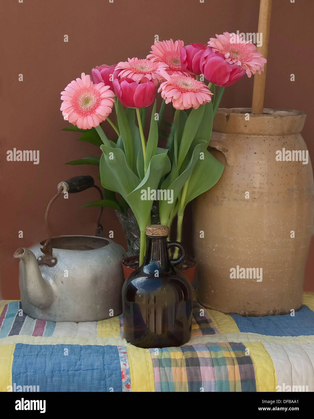 An old tea pot, jug, a butter churn with pink tulips and pink gerber daisies on a quilt. - Stock Image