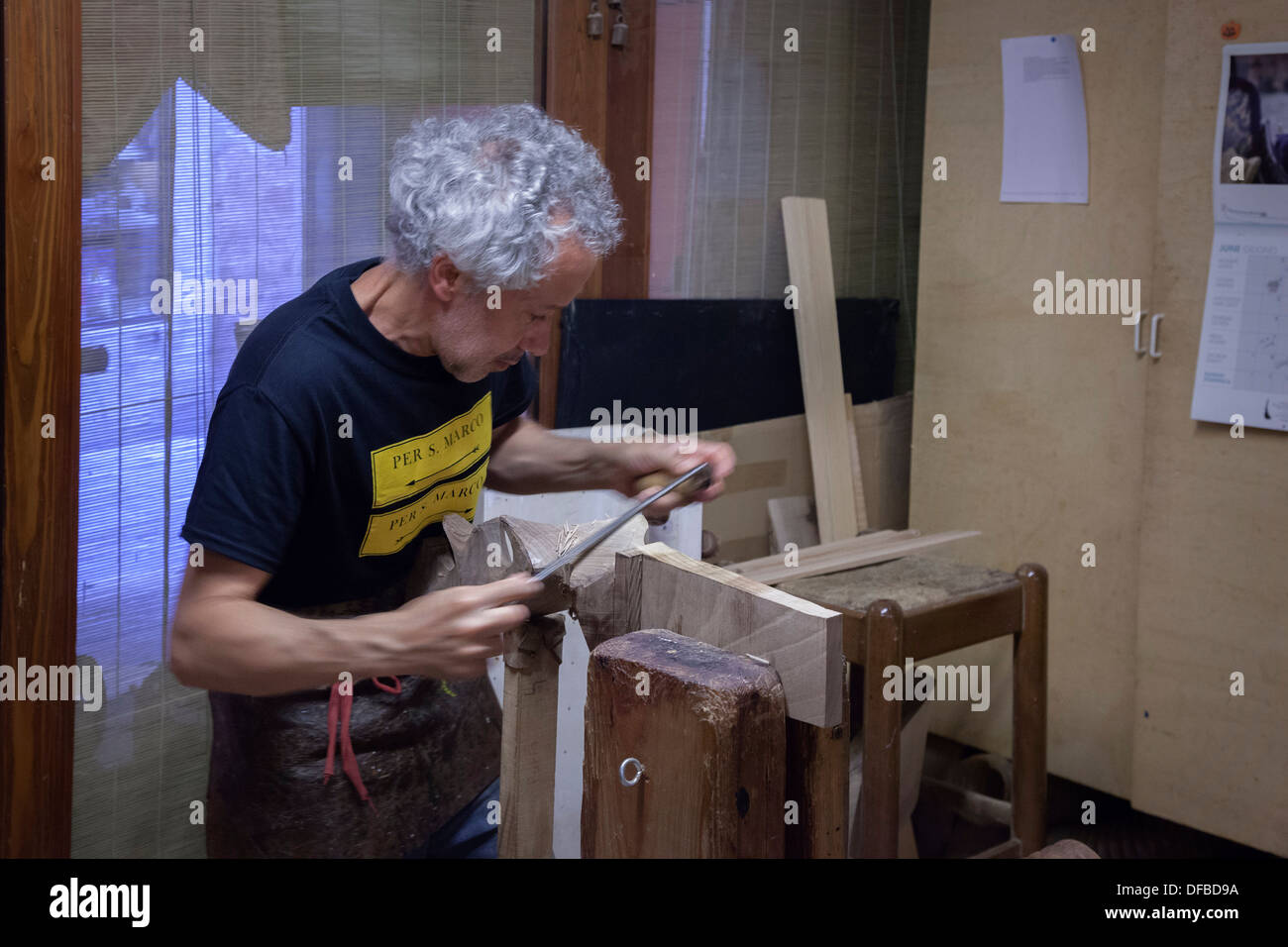 A specialized joiner cutting down to size an oarlock for a Venetian craft known as 'Mascaretta' (Italy). Fabrication de forcole. - Stock Image