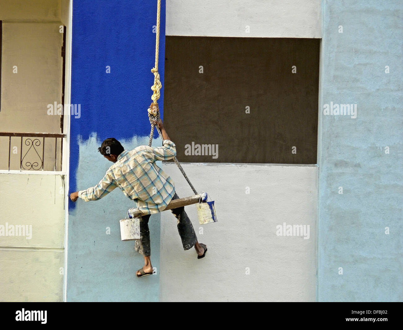 A Painter is seating on a cradle for buildings exterior painting