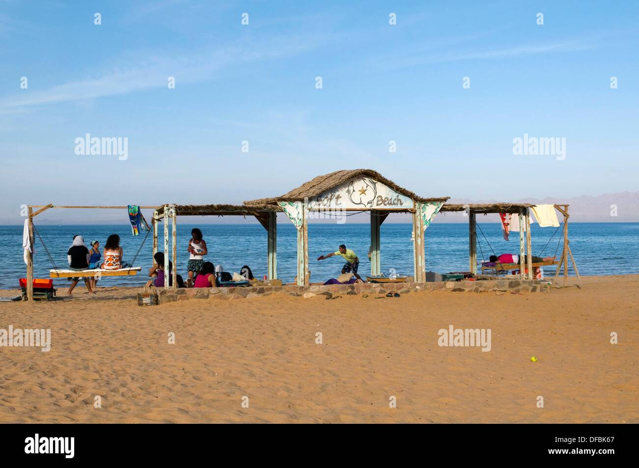 tourists playing on the beach next to the Red Sea in the Sinai Desert of Egypt - Stock Image