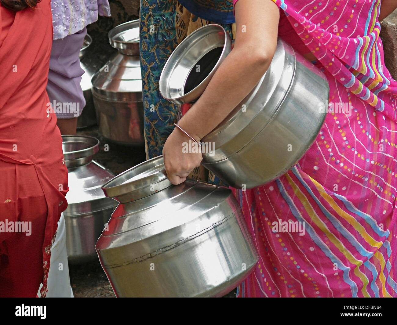 a woman holding vessels in hand is at community water tap pune maharashtra
