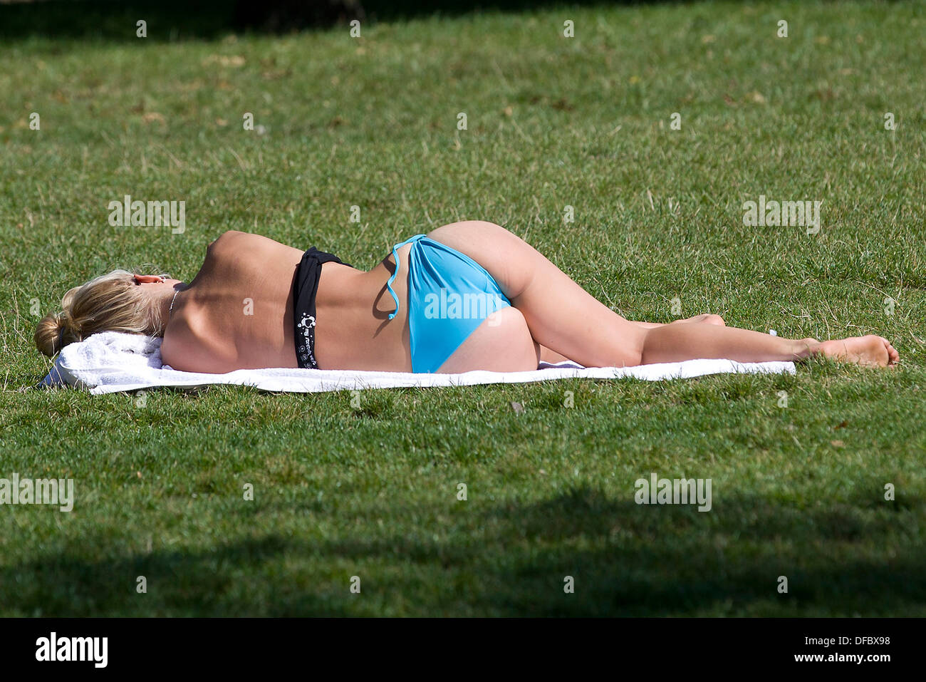 United Kingdom, London : A woman in her bathing costume sunbathes on the grass in Hyde Park in London on August 29, 2013. - Stock Image