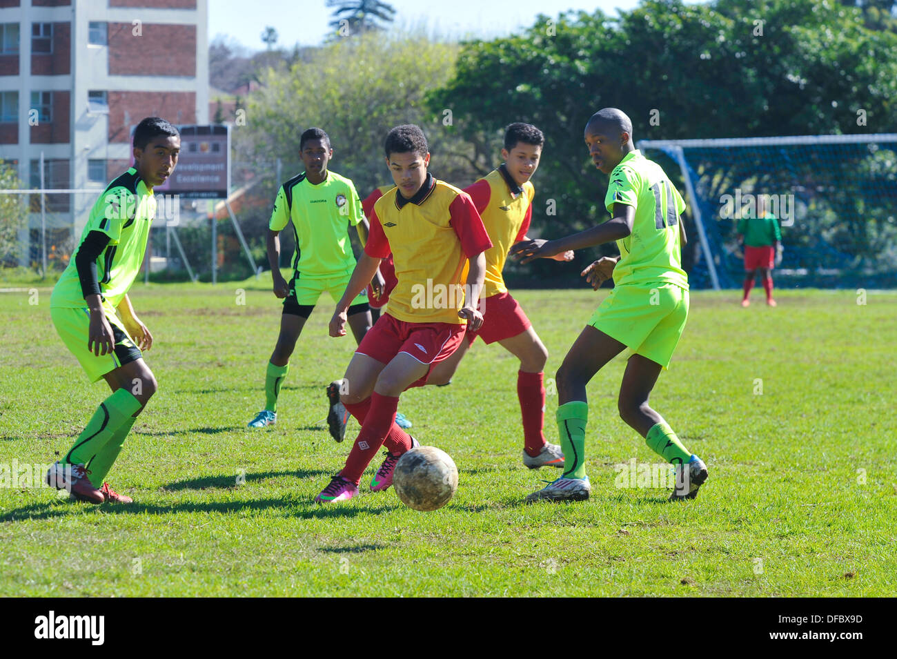 Junior football player protects ball from defenders, Cape Town, Western Cape, South Africa - Stock Image