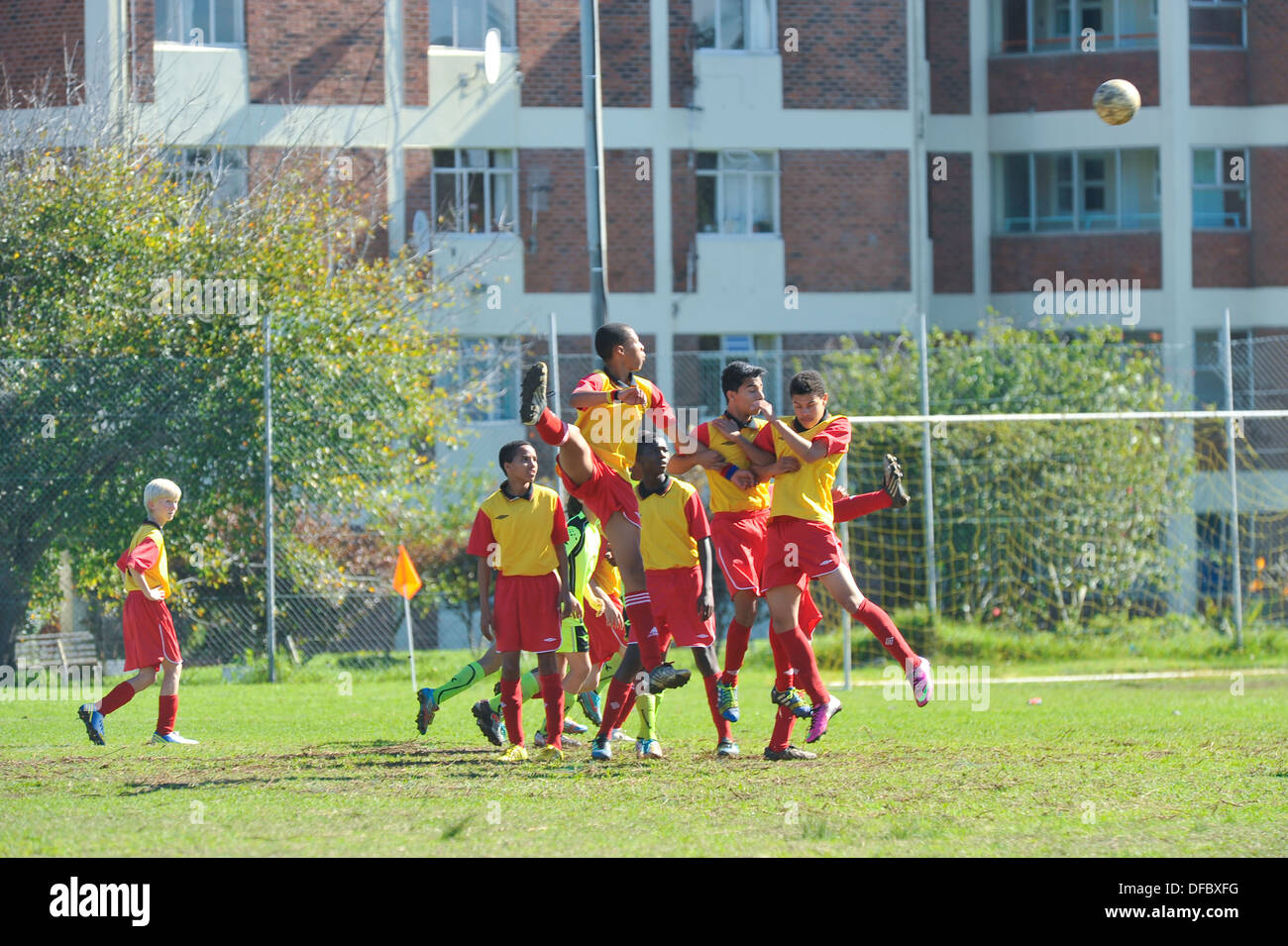 Junior football players jumping to head the ball, Cape Town, Western Cape, South Africa - Stock Image
