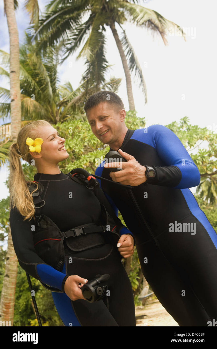 Couple ages 26 and 39 gearing up for scuba diving  Beqa Island, Fiji - Stock Image