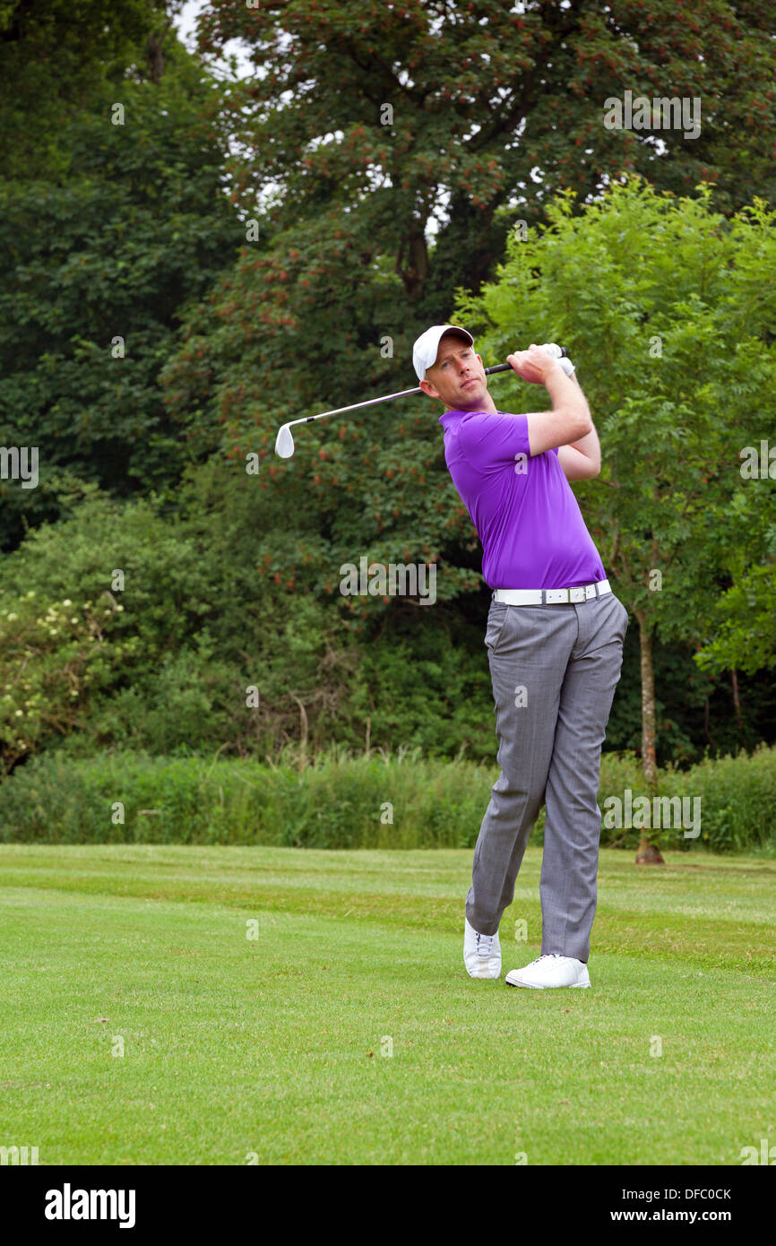 Photo of a golfer addressing the ball and playing a wedge shot into the green. Series of five in the set. - Stock Image