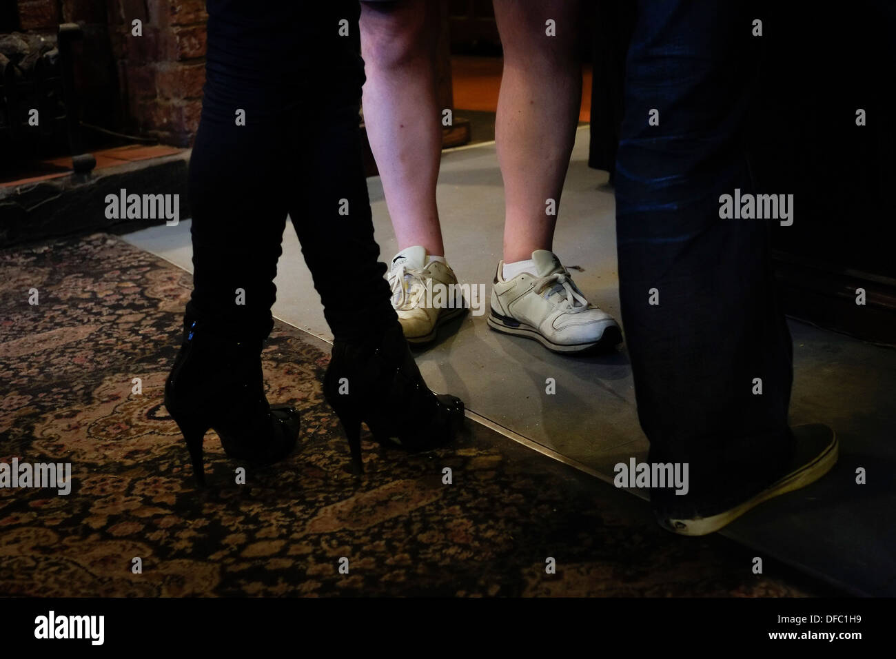 Shoes worn by customers in a pub. - Stock Image