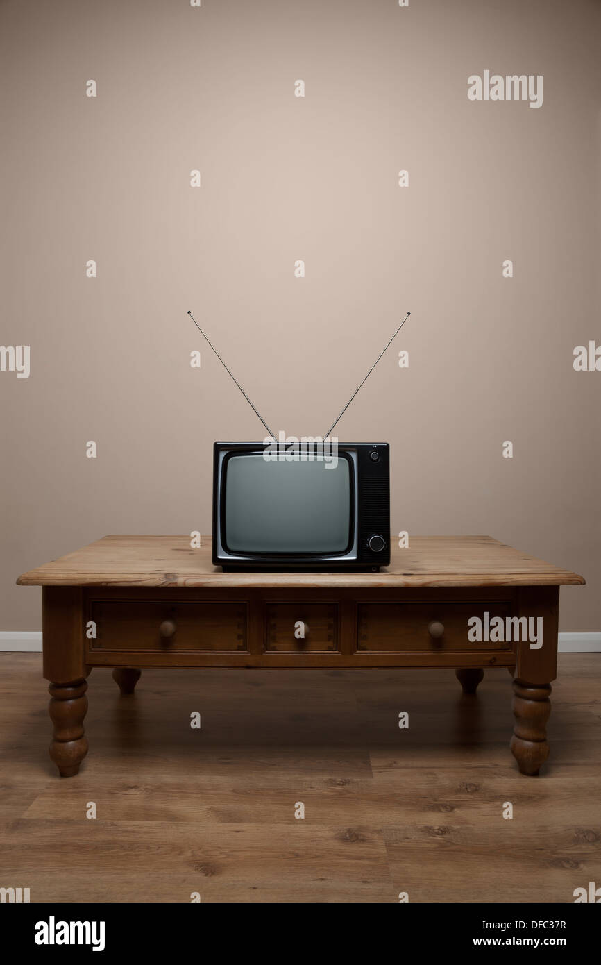 An old retro TV on a table with blank screen in an empty room Stock Photo
