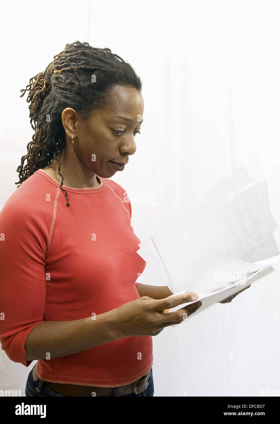 40 year old African American woman with dredlocks in her hair looking over some papers  Side view  Copyspace  Isolated on white - Stock Image