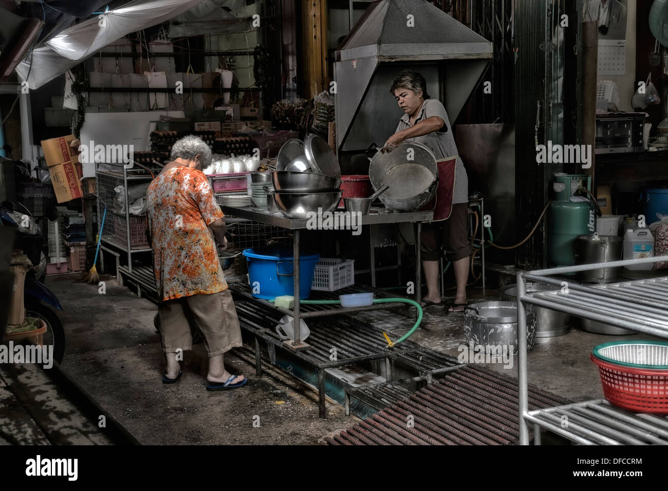 Thailand back street scene of Thai woman washing pots and pans. Thailand S. E. Asia - Stock Image