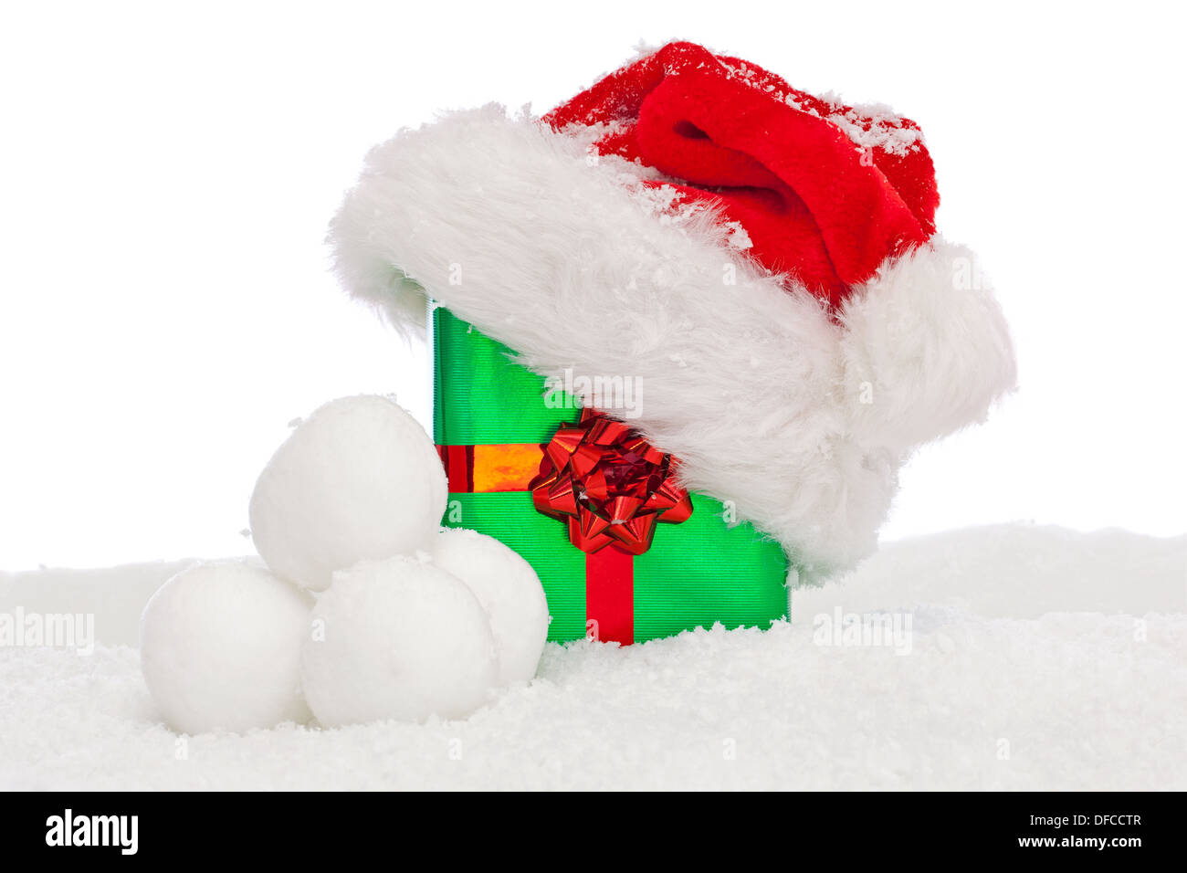 A Santa hat on top of a green gift wrapped Christmas present with ...