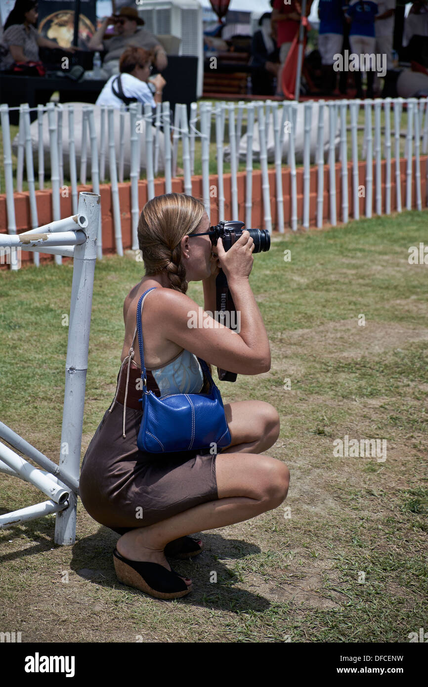 Woman taking photographs from a crouched position - Stock Image