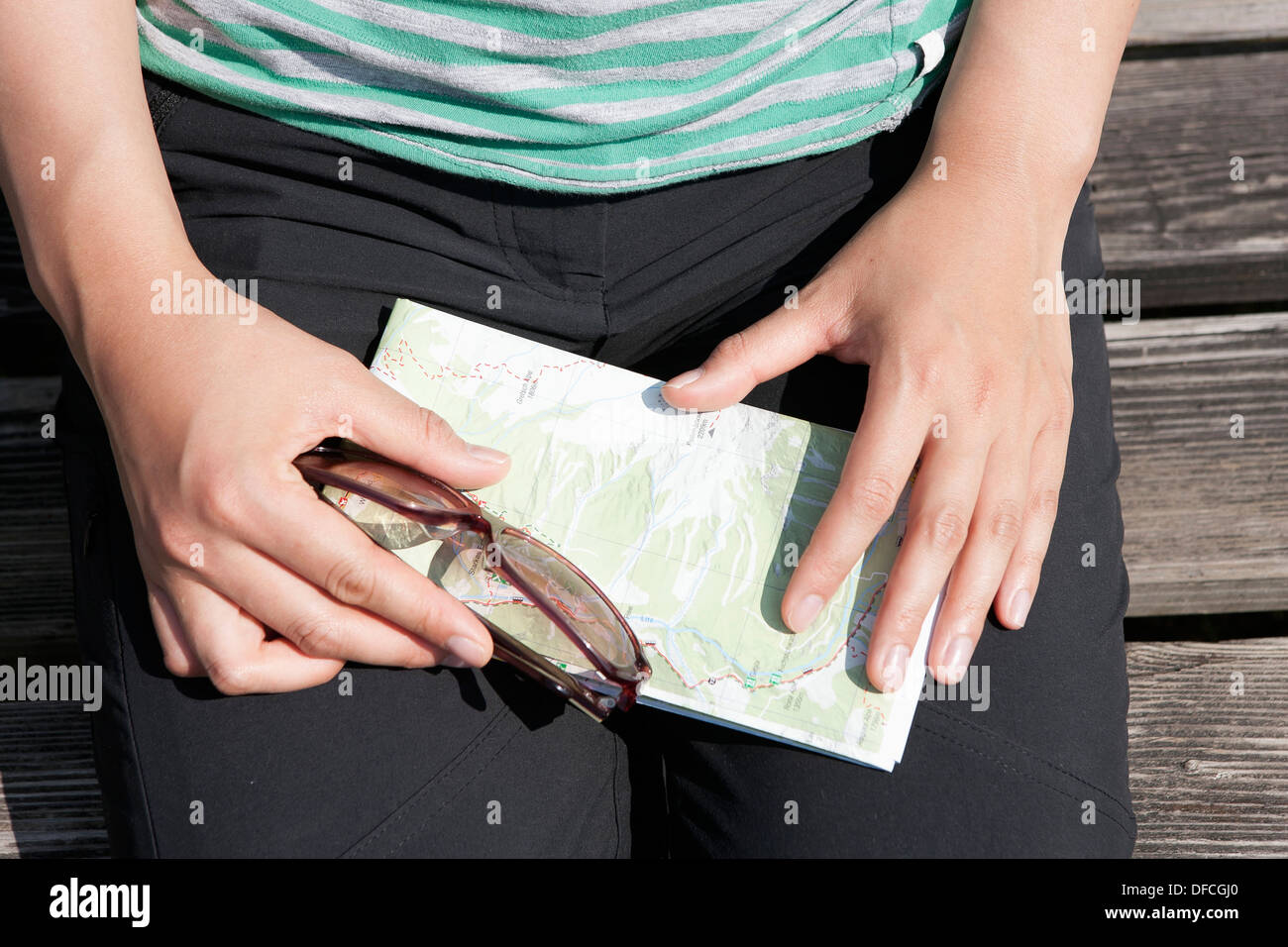 Austria, Young woman holding sunglasses and hiking map, close up - Stock Image
