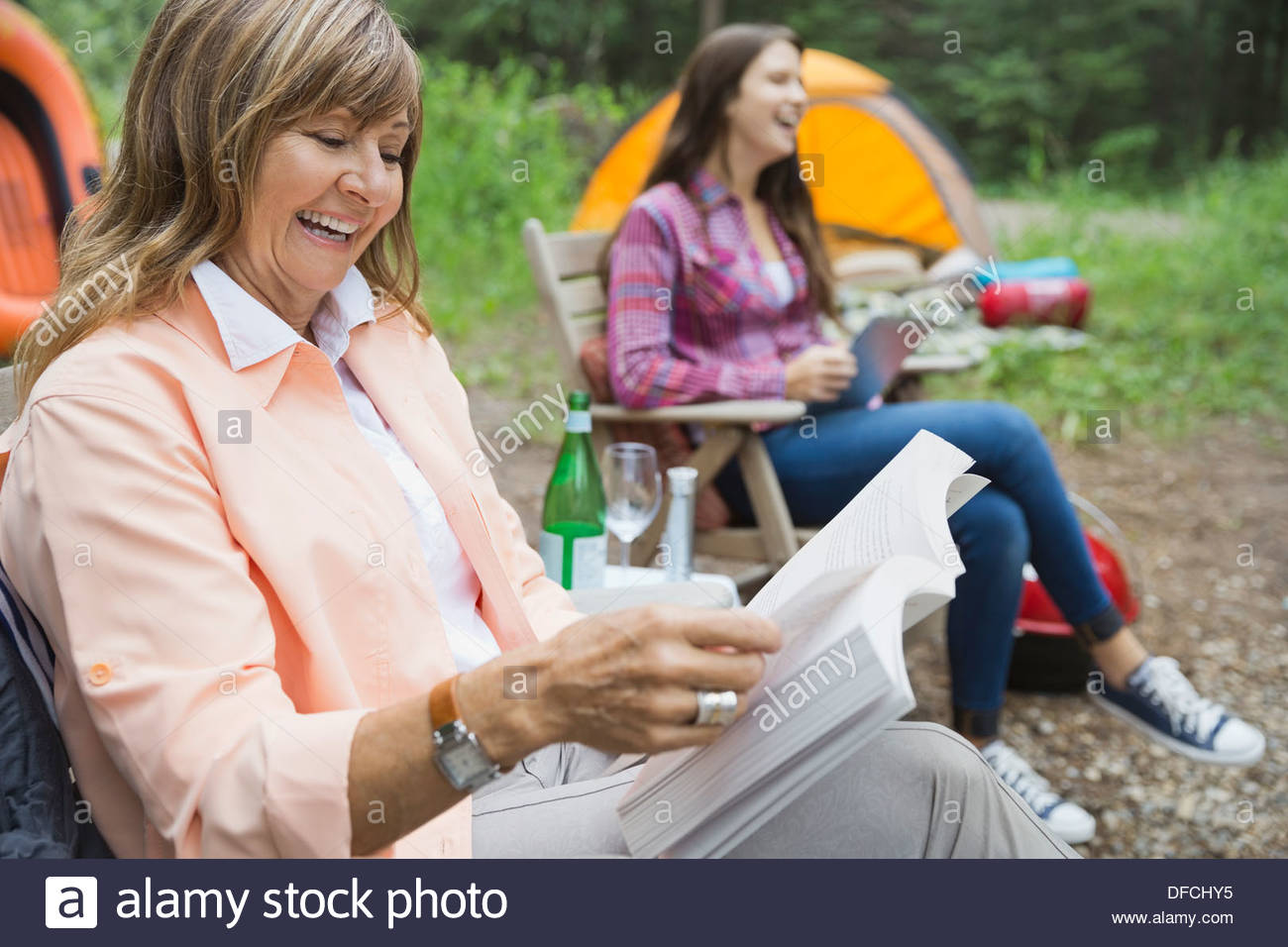 Senior woman reading book at campsite - Stock Image
