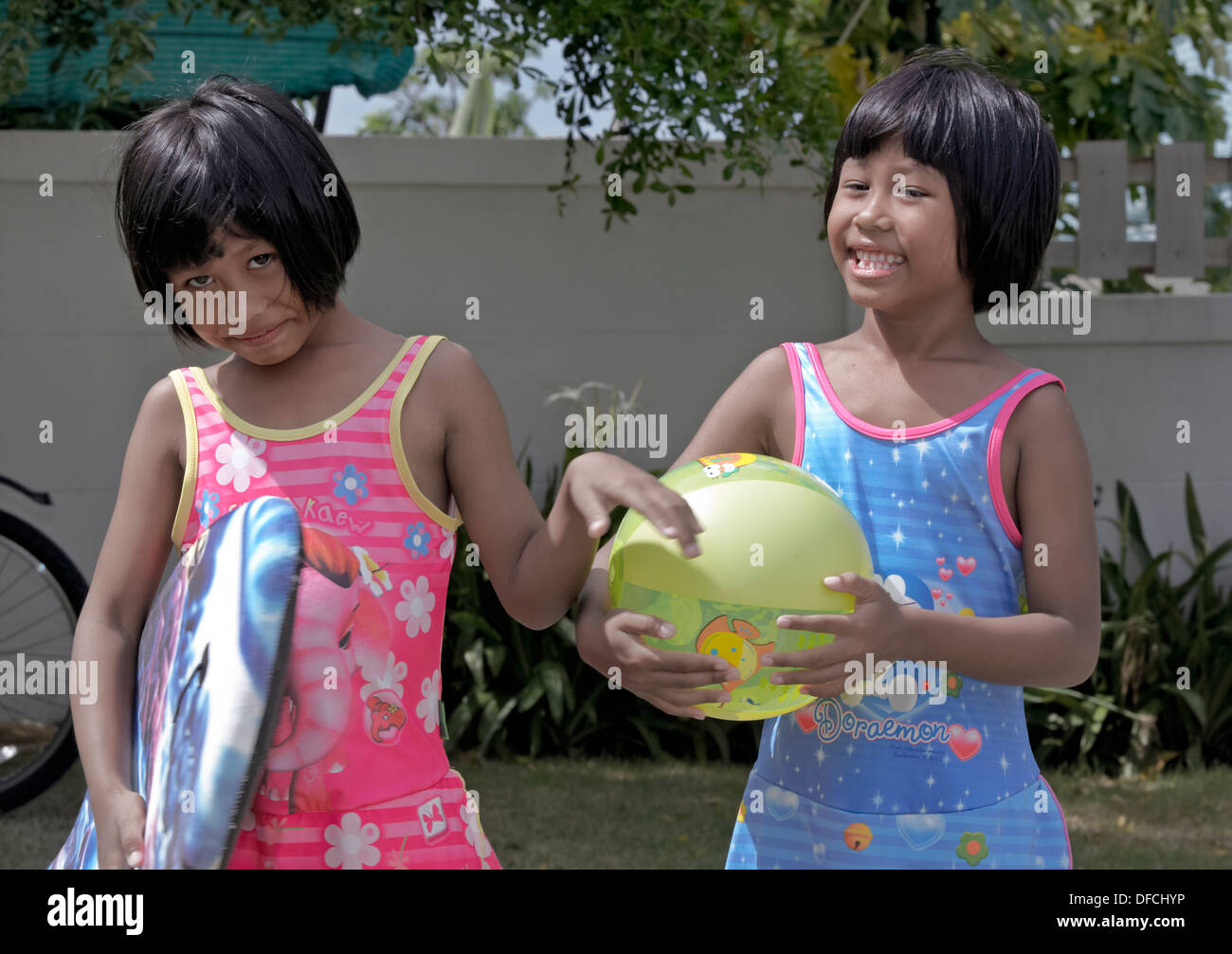 Identical Thai 6 year old twin sisters. Thailand S. E. Asia - Stock Image
