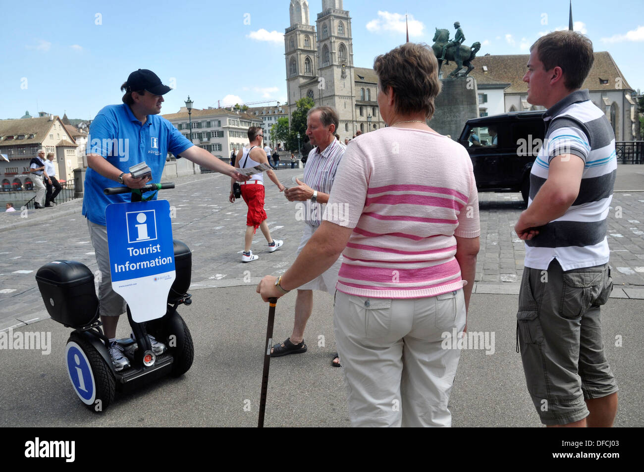 Zurich (Switzerland): a tourism board employee giving information to tourists in the city's center - Stock Image