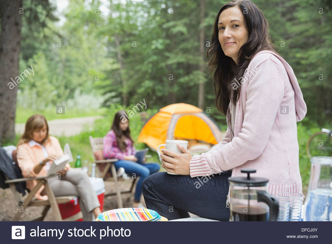 Portrait of woman with coffee mug sitting on table at campsite - Stock Image