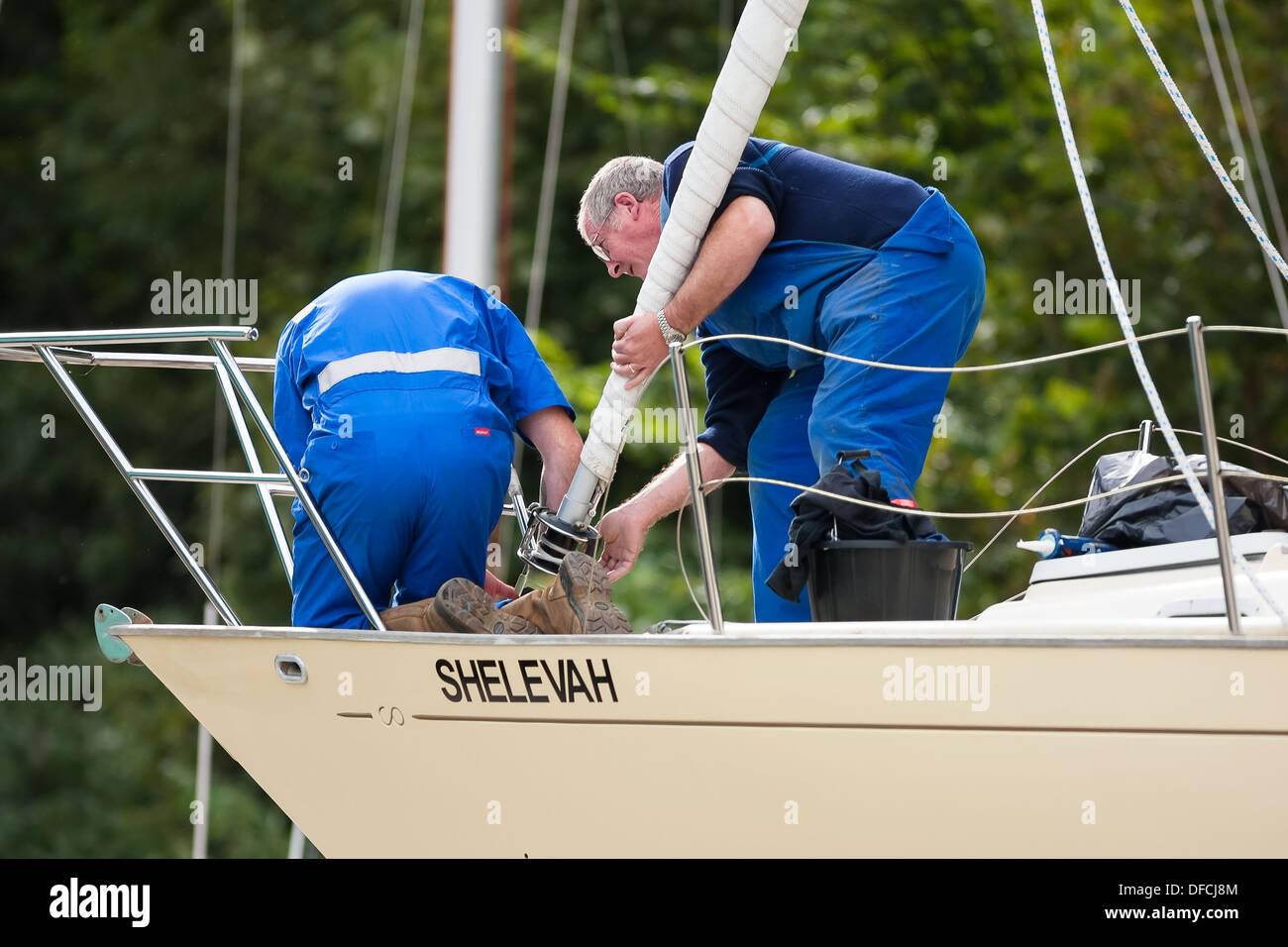 boatyard workmen fixing sail - Stock Image
