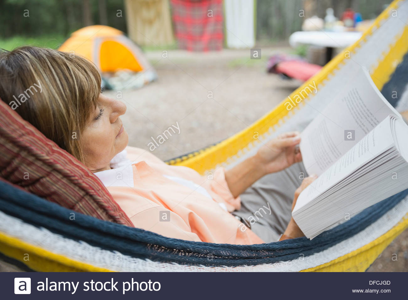 Relaxed senior woman reading book in hammock at campsite - Stock Image