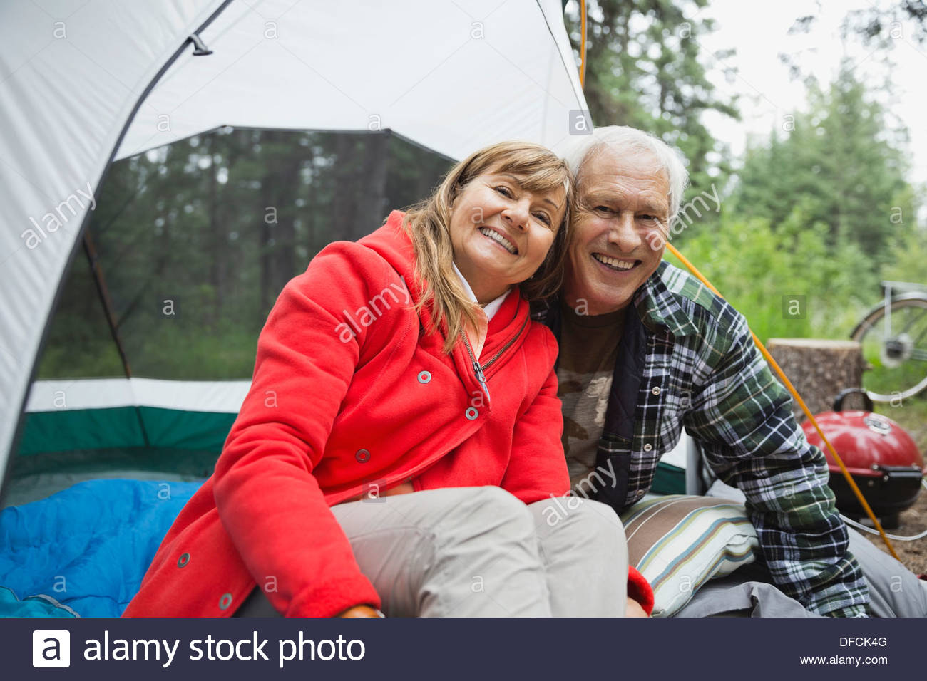 Portrait of happy senior couple sitting in tent at campsite - Stock Image