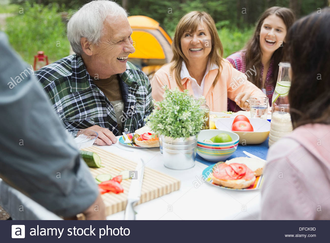 Happy senior couple enjoying meal with family at campsite Stock Photo