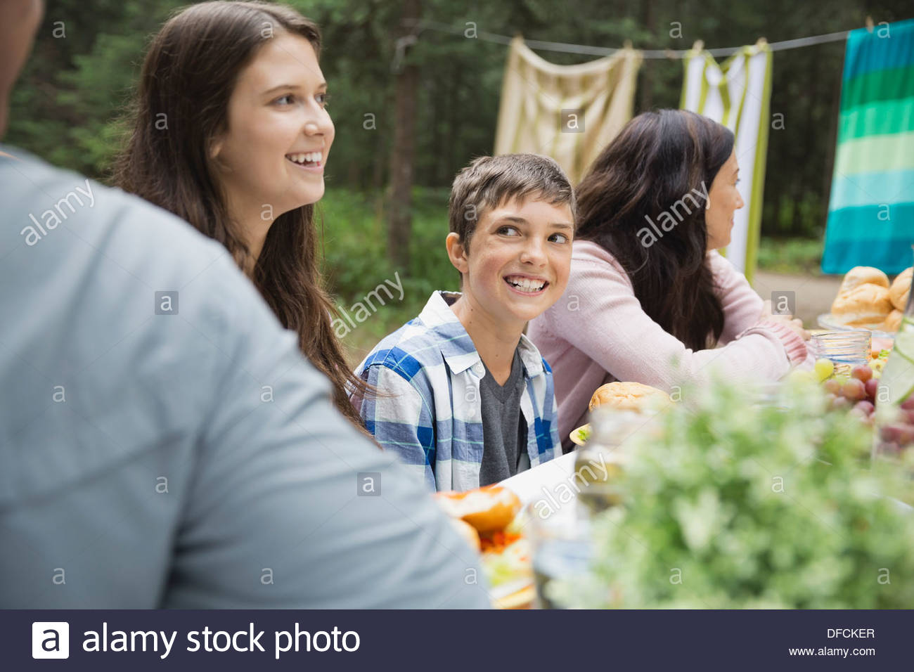 Cheerful boy having food with family at campsite Stock Photo