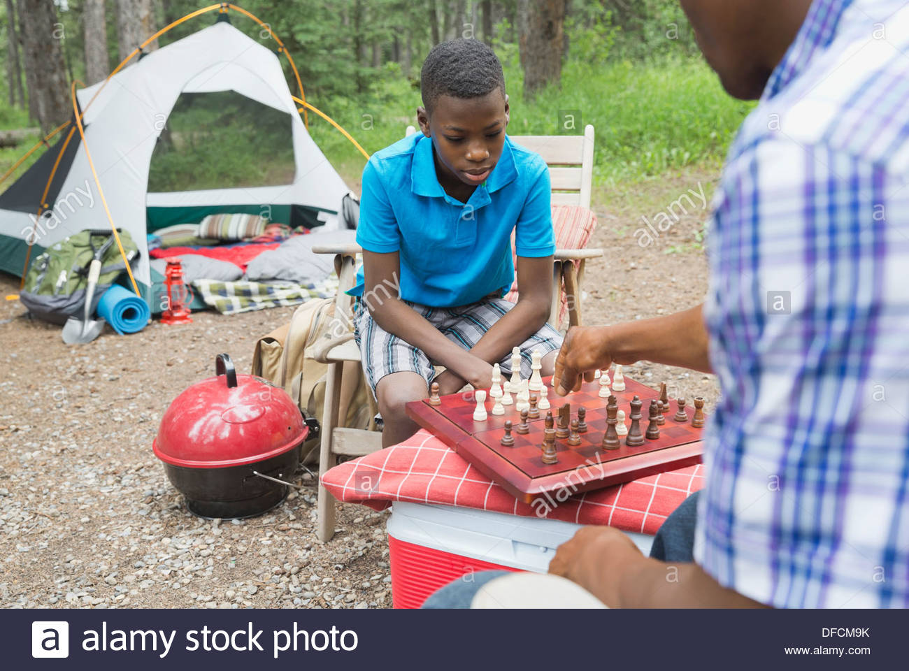 Father and son playing chess at campsite - Stock Image