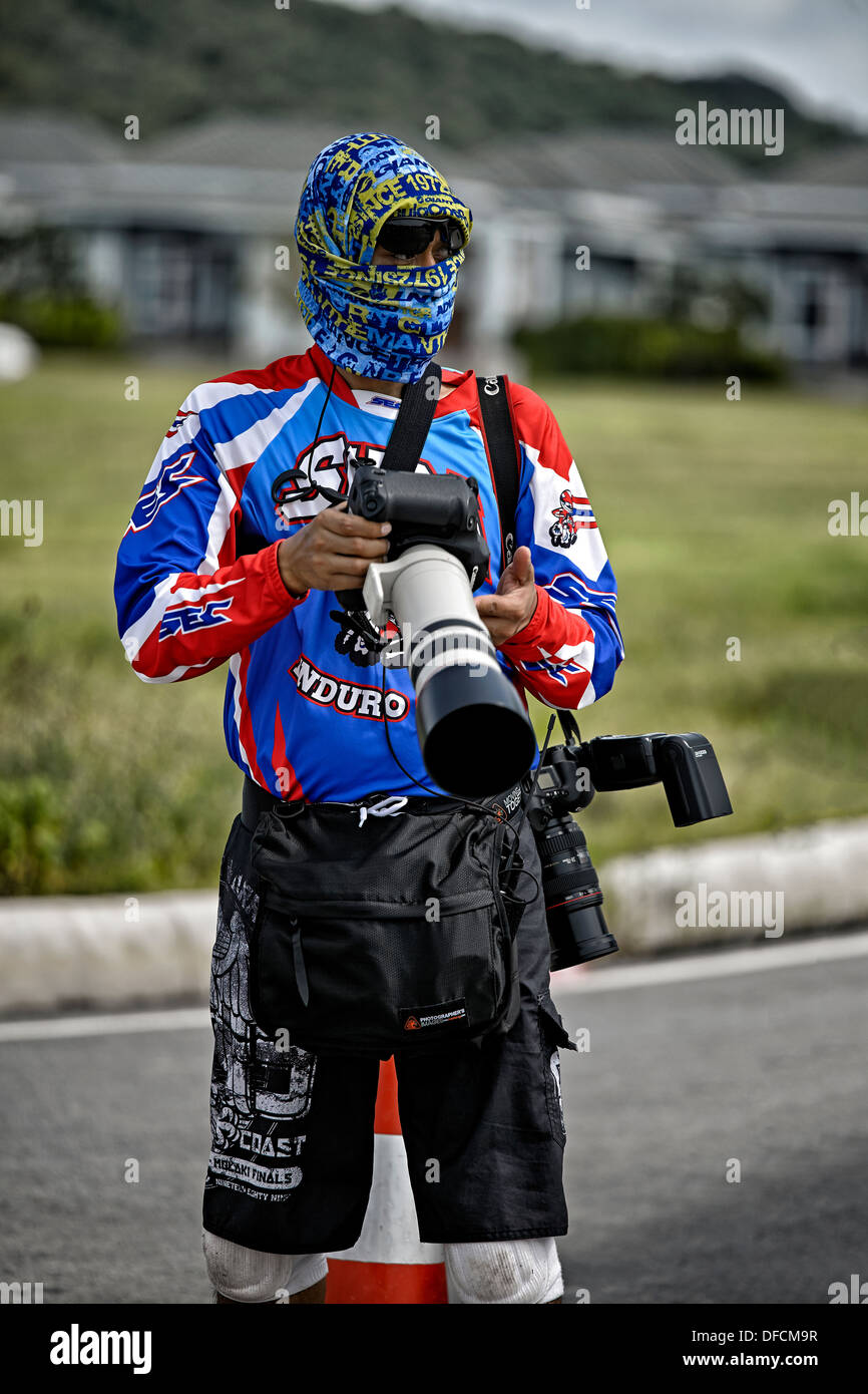 Colorfully attired professional photographer taking photos with an assortment of Canon cameras and lenses. - Stock Image