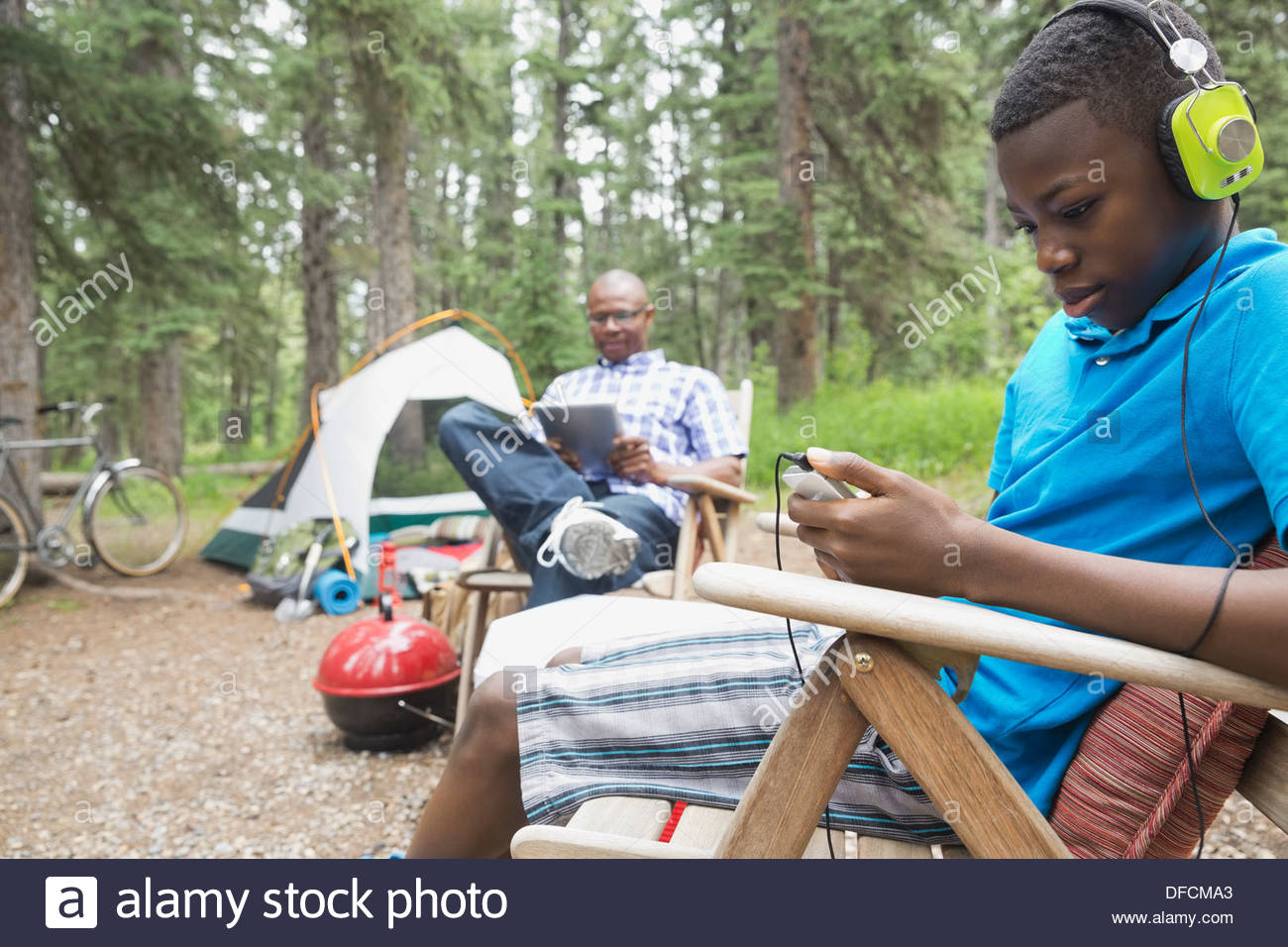 Father and son using technologies at campsite - Stock Image