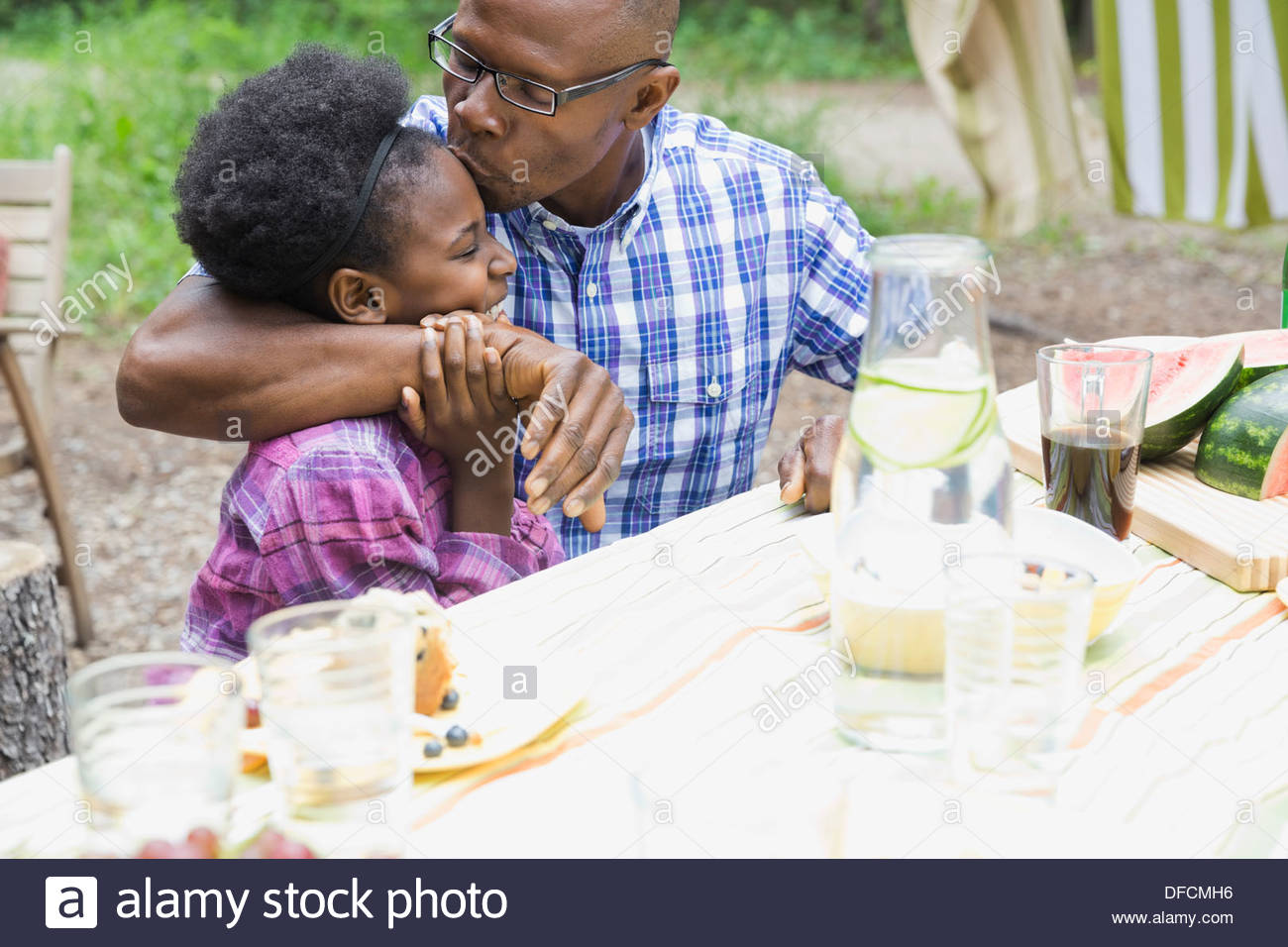 Father kissing daughters forehead outdoors - Stock Image