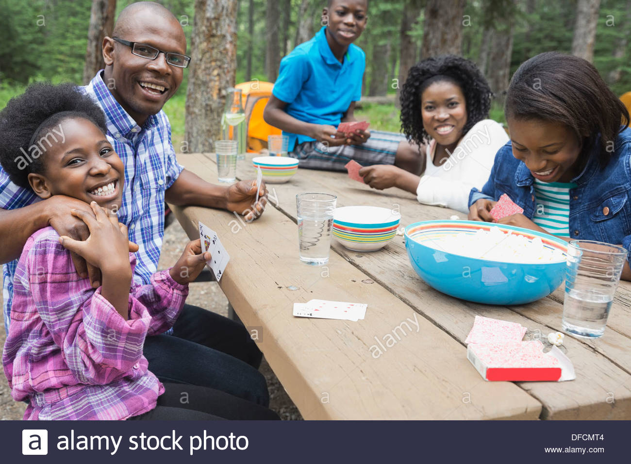 Family of five playing cards at campground - Stock Image
