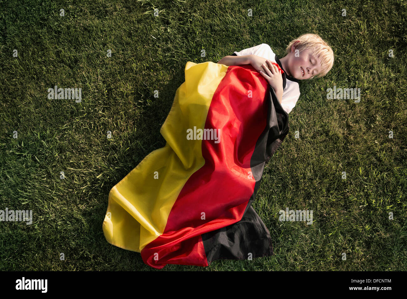 Germany, Cologne, Young football fan sleeping wrapped in German Flag - Stock Image