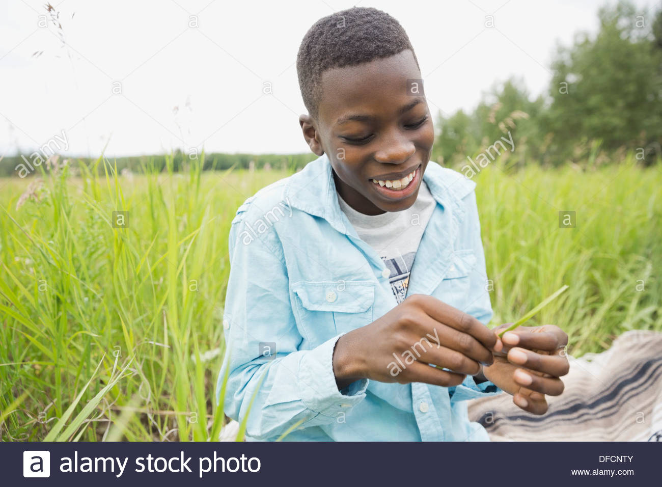 Smiling boy sitting in field - Stock Image