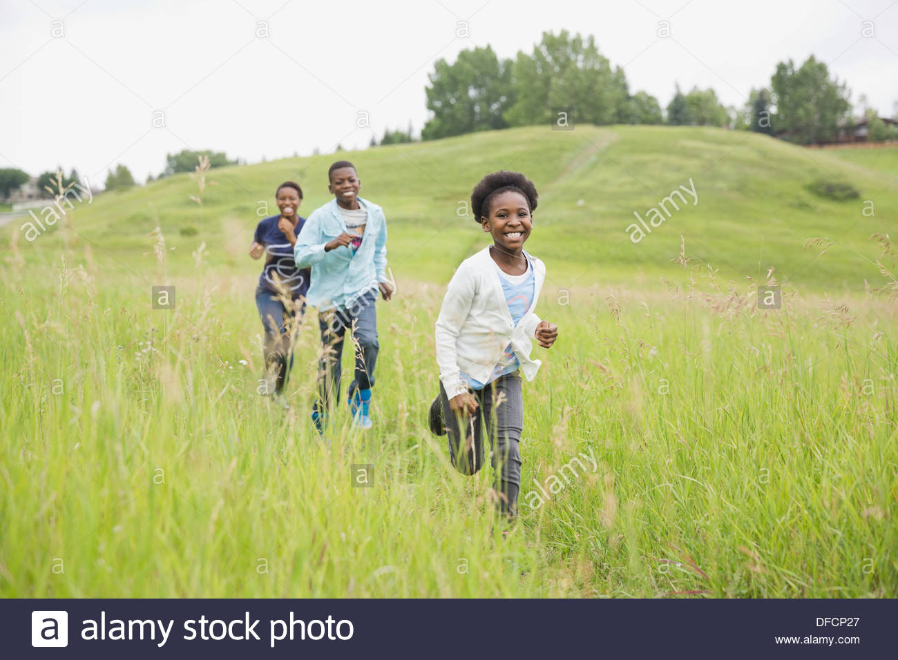 Cheerful siblings running through field - Stock Image