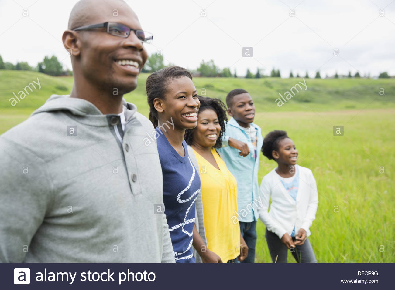 Family of five standing together in field - Stock Image
