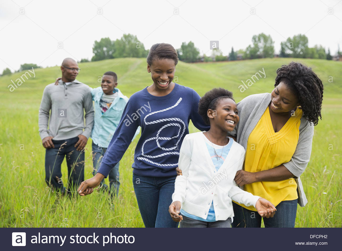 Family walking together through field - Stock Image