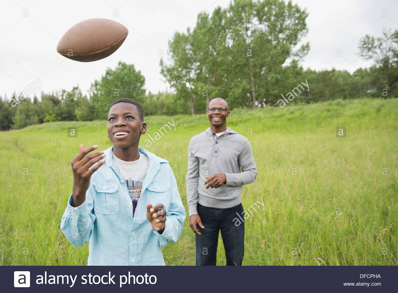 Father and son playing American football outdoors Stock Photo