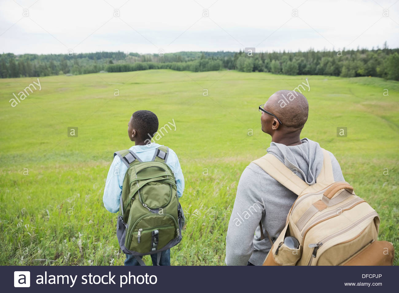 Father and son looking out onto field - Stock Image