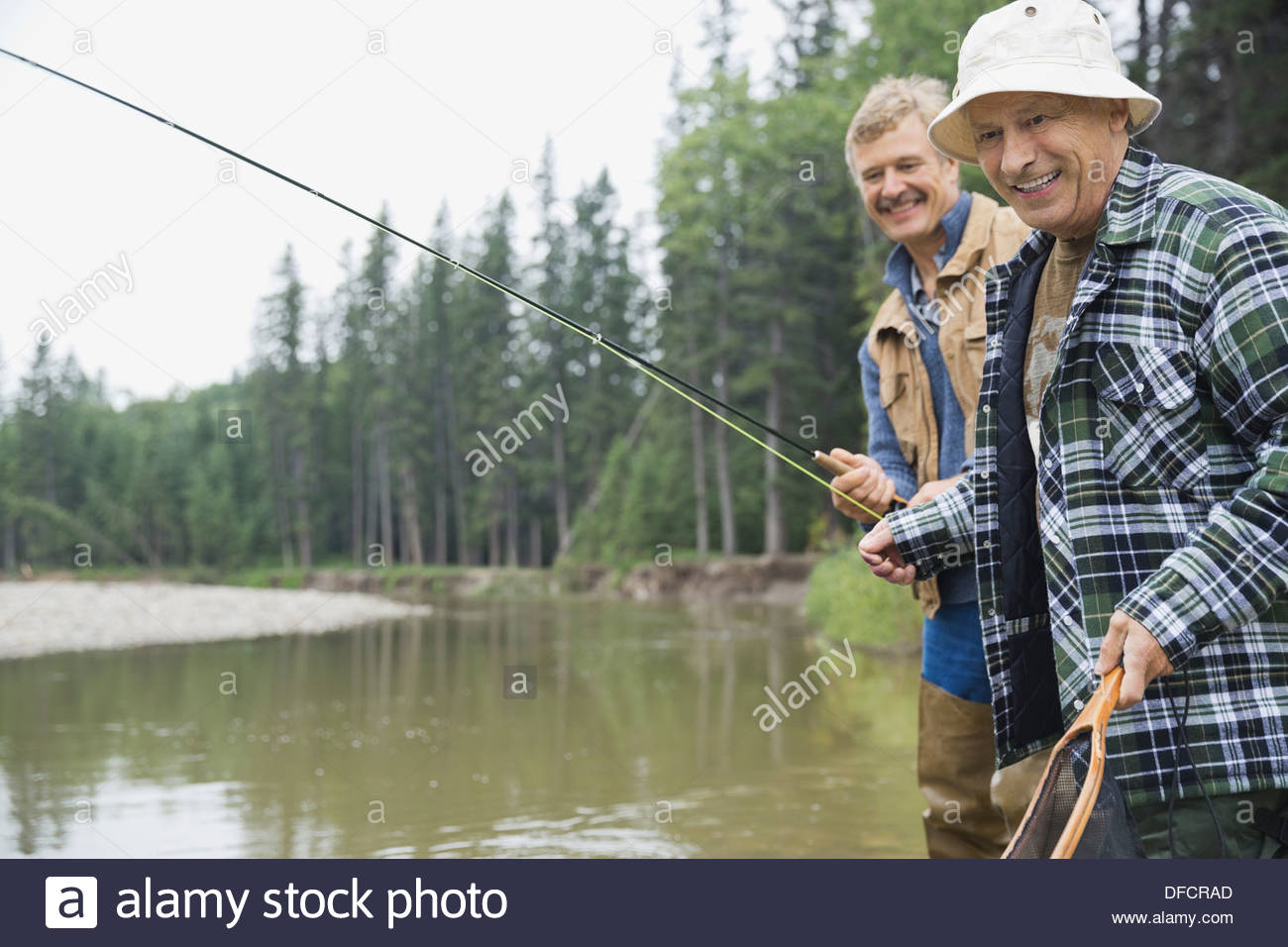 Happy senior man fishing with son - Stock Image