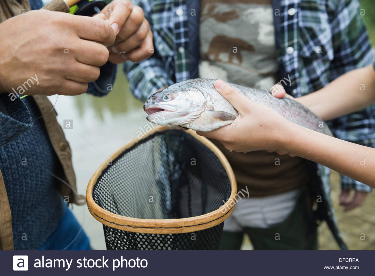 Male family members gathered around caught fish - Stock Image