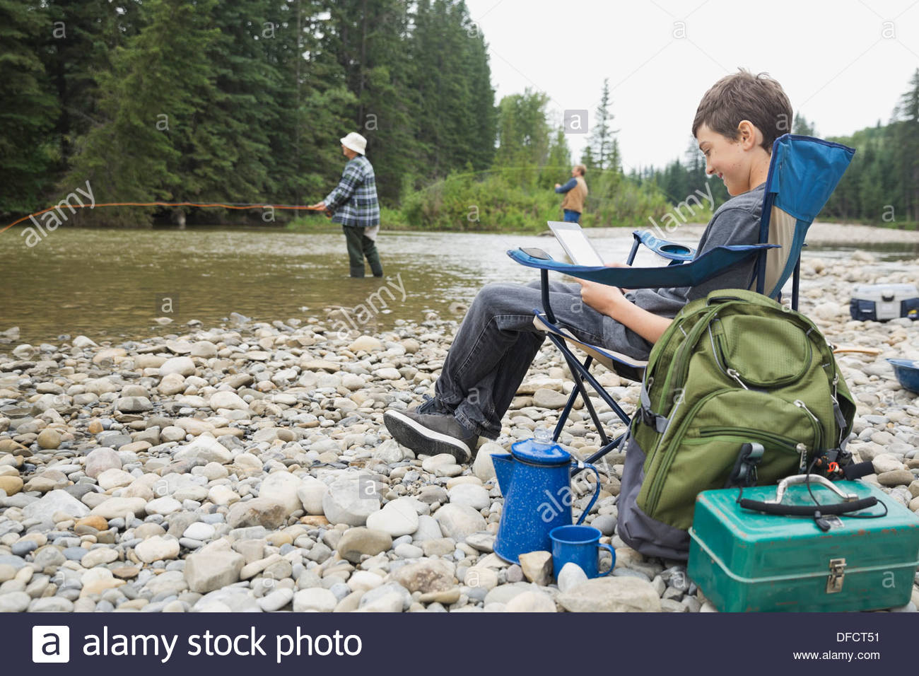 Boy using digital tablet while taking a break from fishing - Stock Image