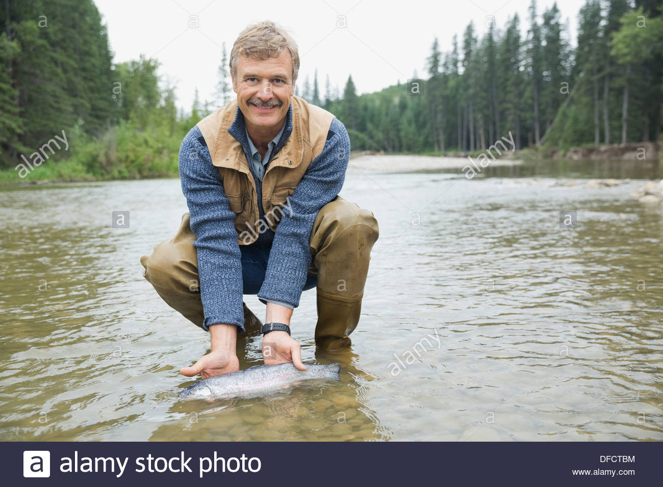Portrait of mature man holding caught fish - Stock Image
