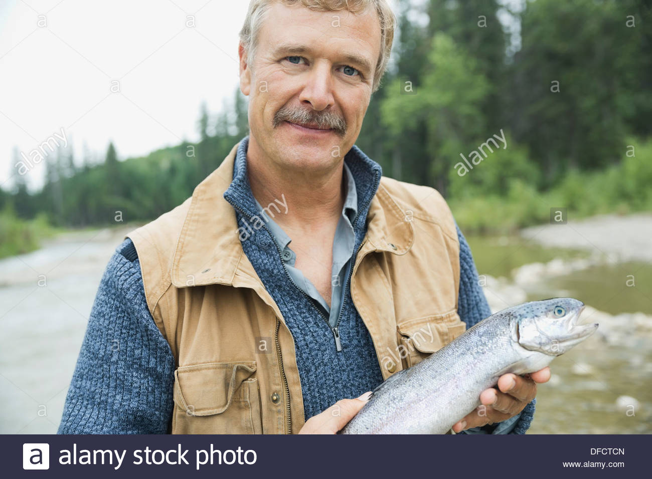 Portrait of mature man holding freshly caught fish - Stock Image
