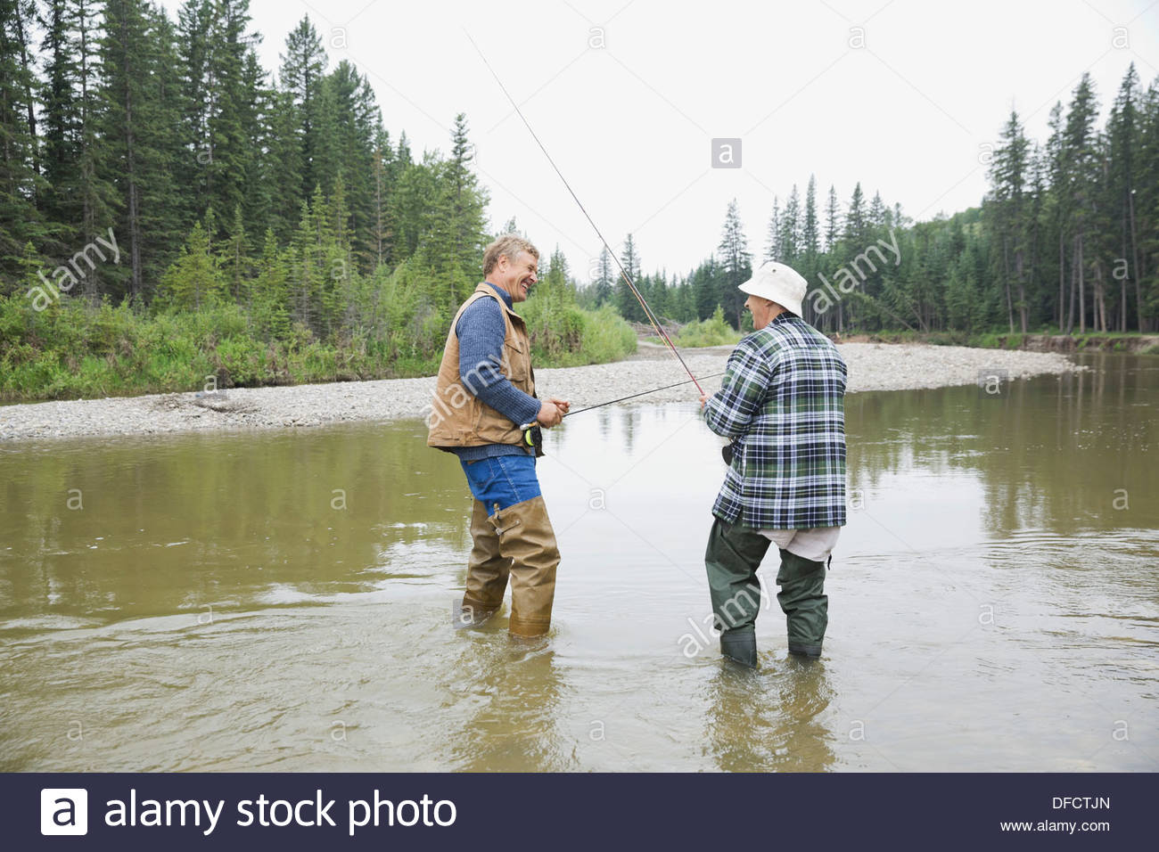 Father and son with fishing rods standing in river - Stock Image
