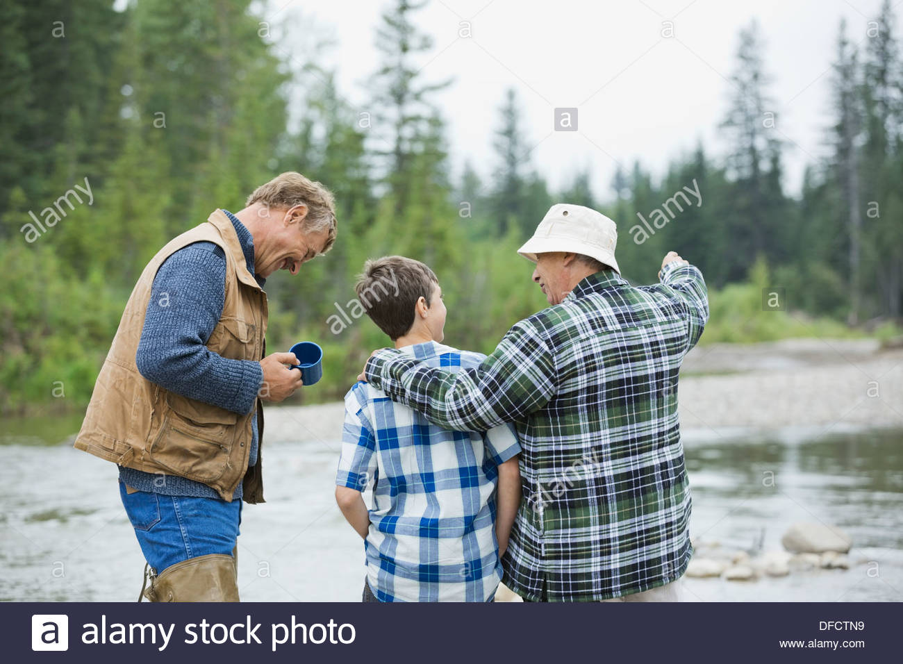 Rear view of male family members near a river Stock Photo